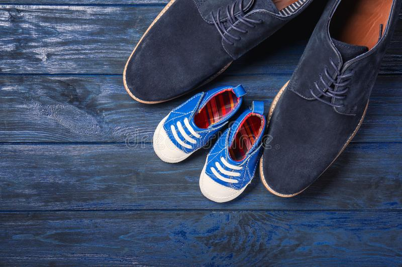 Big and small shoes on wooden background. Father`s day composition stock photography