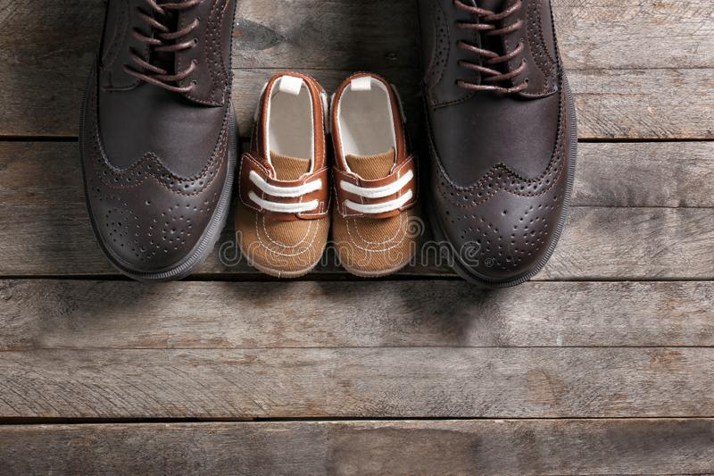 Big and small shoes on wooden background. Father's day stock photography