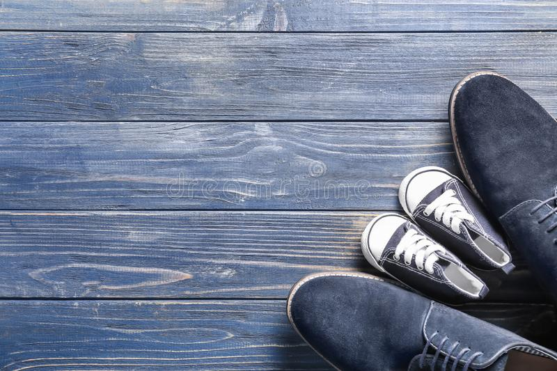 Big and small shoes on wooden background. Father\'s day celebration royalty free stock photos