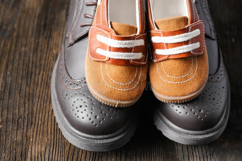 Big and small shoes on wooden background. Father's day celebration royalty free stock photography
