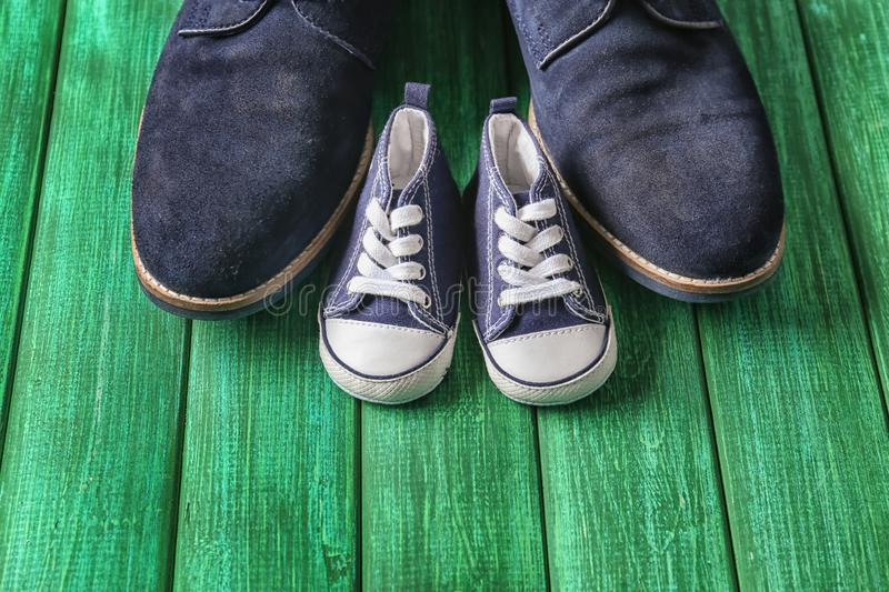 Big and small shoes on wooden background. Father\'s day celebration stock image