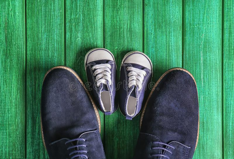 Big and small shoes on wooden background. Father's day celebration royalty free stock images
