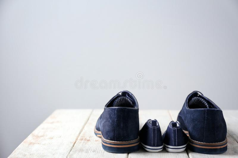 Big and small shoes on wooden table against light background. Father's day royalty free stock images