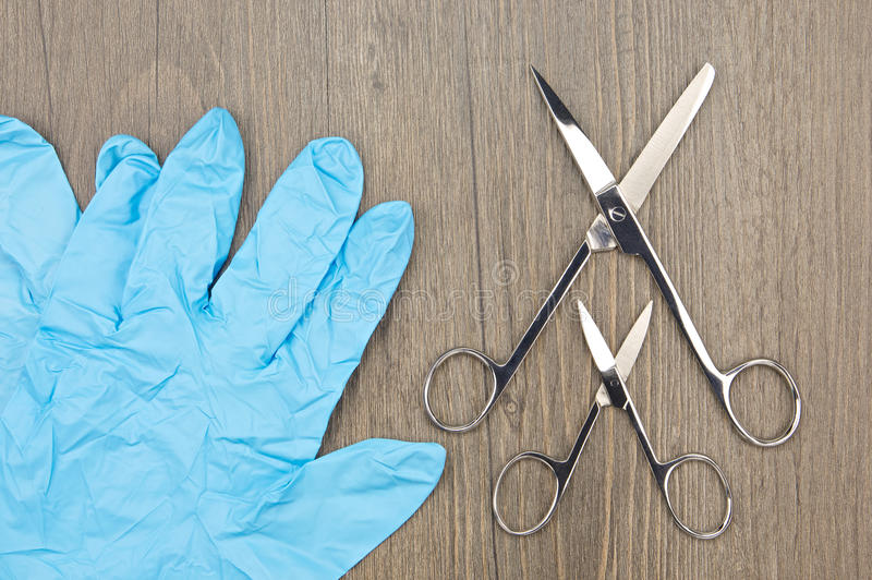 Big and small silver surgical scissors with blue latex glove. Big and small silver surgical scissors place beside blue latex glove on wood background royalty free stock photos