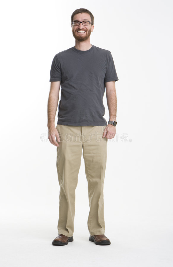 Big Smile. Bearded man wearing gray t-shirt and khaki pants standing in white photo studio with a big smile royalty free stock photography