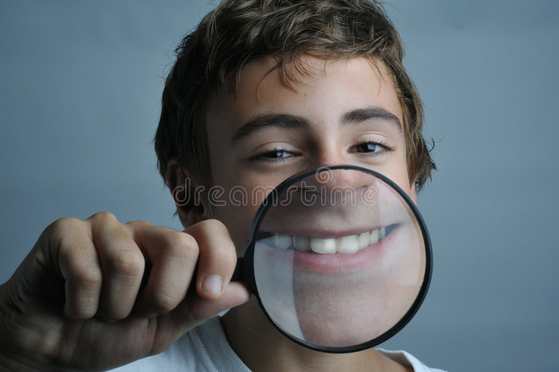 Big smile. Portrait of a boy showing his dent through a magnifier royalty free stock images