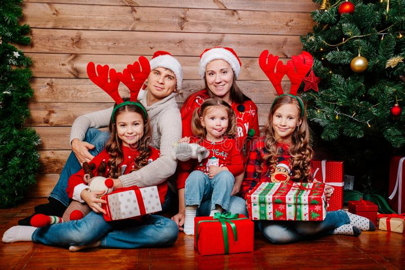 Big smiling family in santa hats with many gift boxes sittting near Christmas tree at home. Merry Christmas and Happy royalty free stock photography