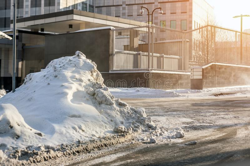 Big snowdrift on city street after heavy snowfall in winter. Heap of dirty snow near office building, blizzard aftermath. Weather royalty free stock images