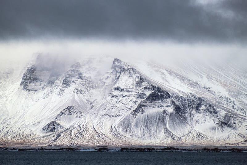 Big snowy mountain in Reykjavik Iceland. Big snowy mountain with dark clouds in stormy winter weather in Reykjavik Iceland stock photography