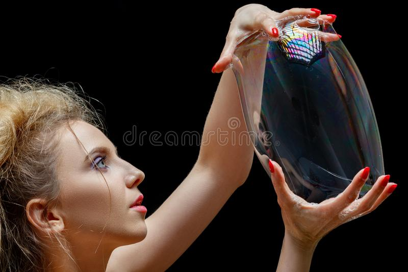 Big soap bubble. Girl make with big soap bubble on black background, profile view royalty free stock image