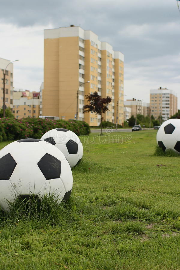 Big soccer balls on the green lawn stock image