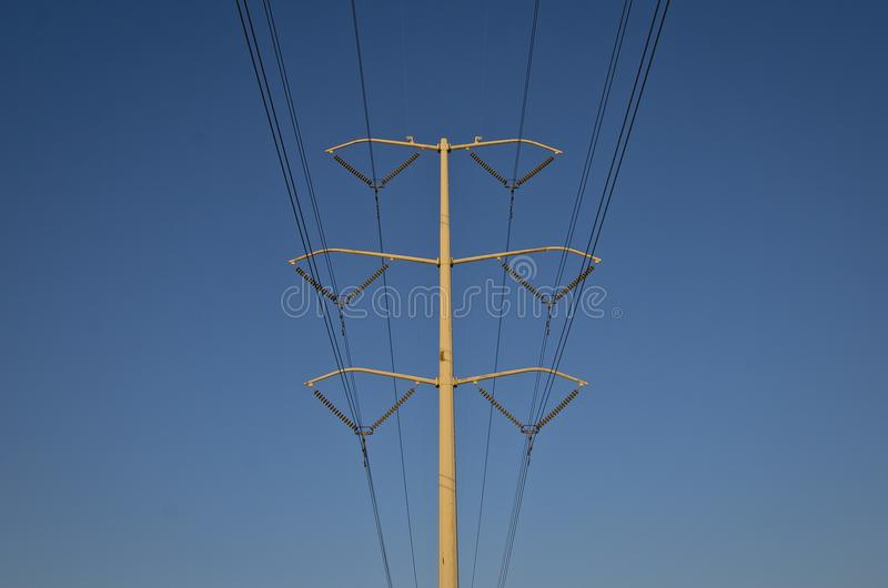 A big solo power line and pole in the blue sky. The big solo power line in the clear and empty blue summer sky as the lines cut through royalty free stock image