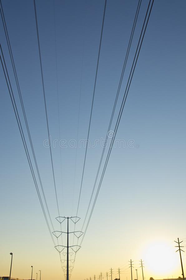 A big solo power line and pole in the blue and yellow sky. The big solo power line in the clear and empty blue and yellow summer sky as the lines cut through stock photo