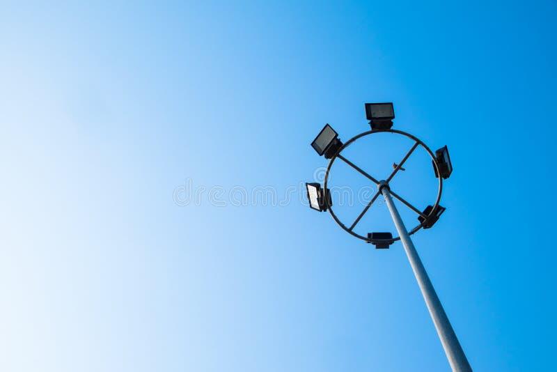 Big spotlight pole on blue sky. Background stock photo