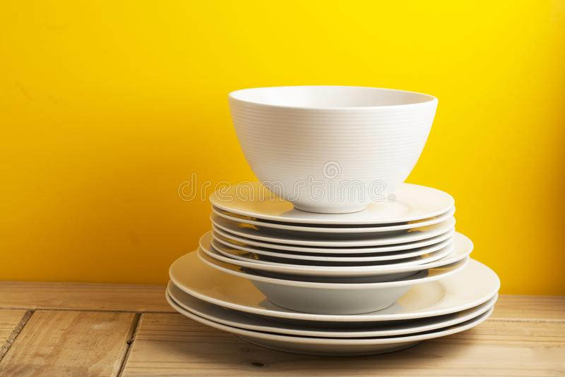 Big stack of different white plates, bowls, isoalted yellow background, one above the another. Wooden table, Copy Space. Big stack of different white plates stock photos