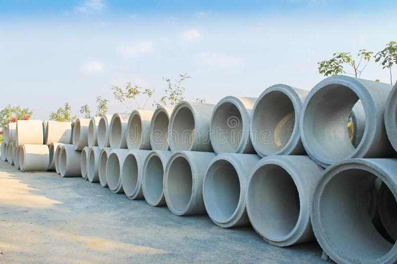 Big stacks of concrete sewage pipes on the ground prepare for underground instalation and blue sky background royalty free stock photography