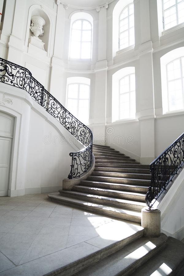 Big staircase with openwork metal curved banister inside royalty free stock image