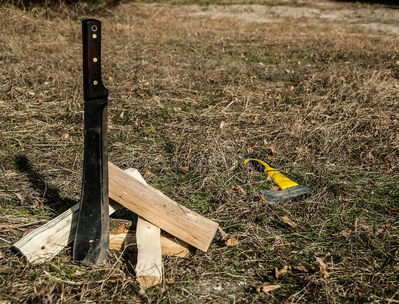 Big steel knife or machete stuck in the ground, firewood and axe lying on the grass. stock image