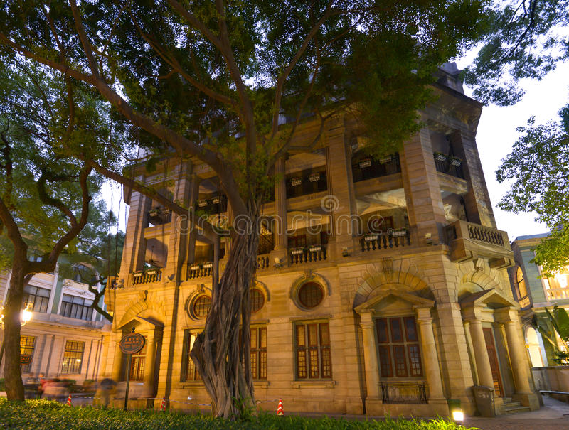 Big stone colonial building, Shamian Island, Guangzhou city, Guangdong, China. Big stone colonial building at the evening with banyan tree in front of it stock photography