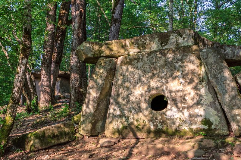 Big stone Pshada dolmen in summer Caucasus mountain forest on sunny day. Ancient megalithic tomb with large flat stone slabs and royalty free stock photography