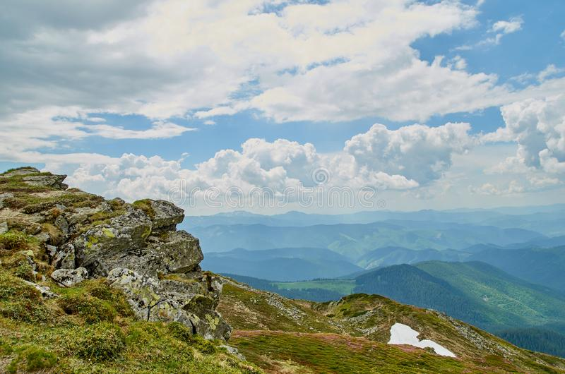A big stone scaur and green hills in Carpathian mountains in the summer. Mountains landscape background stock photo