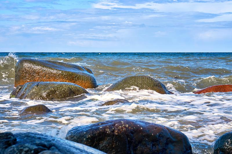 Big stones in the Baltic Sea with foaming waves on the shore stock image