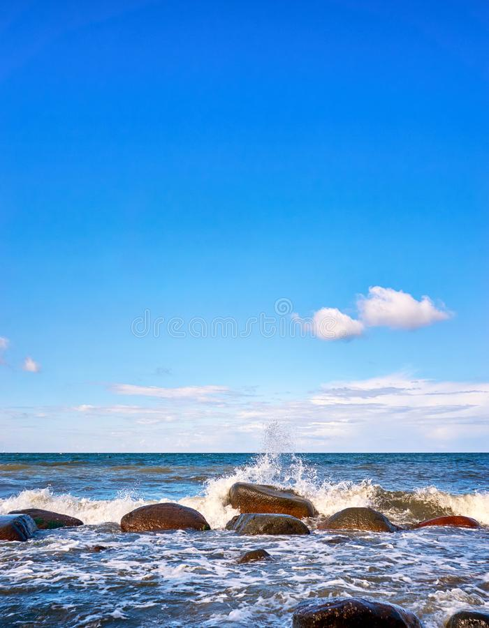 Big stones with foaming waves under blue sky with clouds. Baltic Sea in Mecklenburg-Vorpommern. Beautiful, beauty, nature, outdoors, sand, undulate, water royalty free stock photography