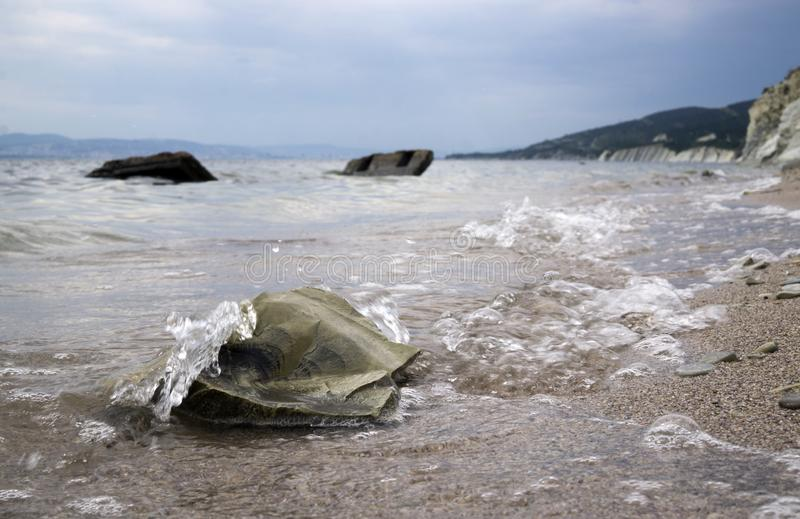 Big stones on the sea shore. Wet sand, transparent water. Overcast cloudy sky. Vacation background stock photography