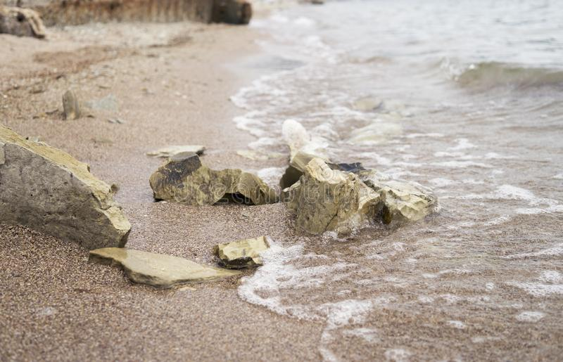 Big stones on wet sand at the sea coast. royalty free stock photography