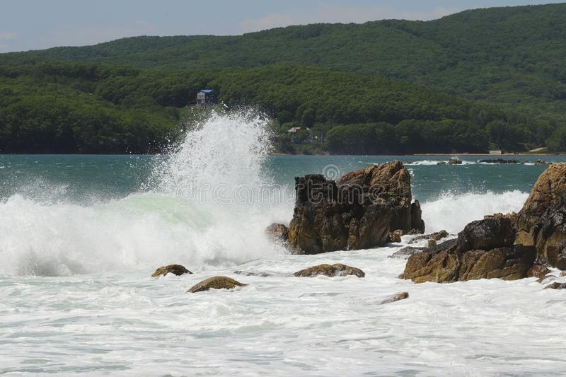 Big storm waves hitting the coastal rocks of the sea. Sunny windy day, blue sky. Splashes and foam. Storm landscape. royalty free stock image