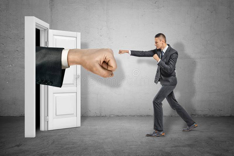 Big stretched fist appearing through white doorway and businessman making kicking gesture on grey wall background. Business and management. Way to success stock photo