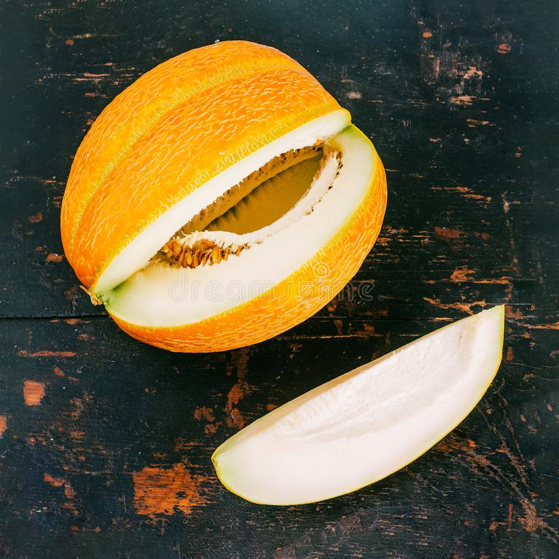 Big striped ripe yellow melon with cut piece close up on black wooden retro background stock images
