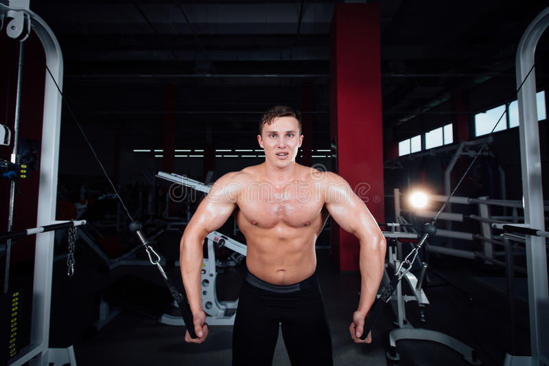 Big strong bodybuider without shirts demonstrate crossover exercises. The pectoral muscles and hard training stock photos