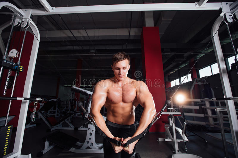 Big strong bodybuider without shirts demonstrate crossover exercises. The pectoral muscles and hard training royalty free stock photography