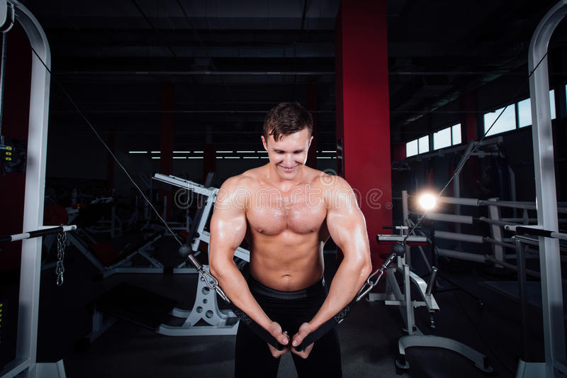 Big strong bodybuider without shirts demonstrate crossover exercises. The pectoral muscles and hard training royalty free stock photo