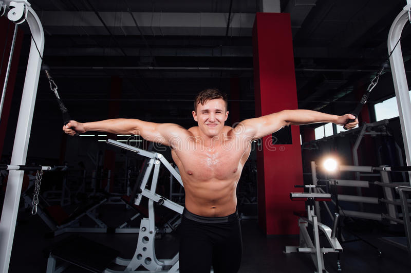 Big strong bodybuider without shirts demonstrate crossover exercises. The pectoral muscles and hard training royalty free stock photos