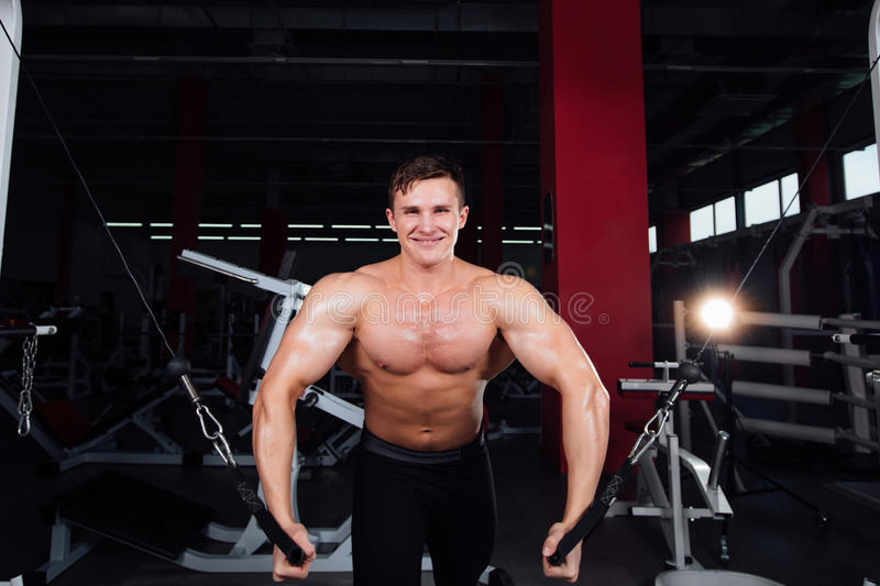 Big strong bodybuider without shirts demonstrate crossover exercises. The pectoral muscles and hard training stock photography