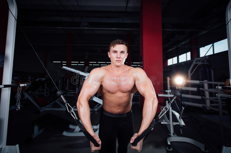 Big strong bodybuider without shirts demonstrate crossover exercises. The pectoral muscles and hard training stock images
