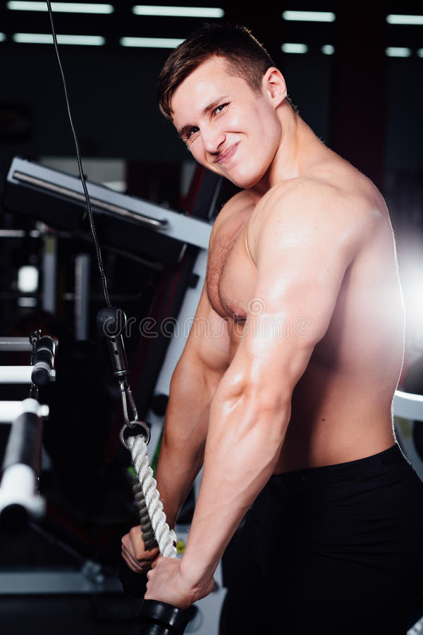 Big strong bodybuider without shirts demonstrate crossover exercises. The pectoral muscles and hard training royalty free stock images