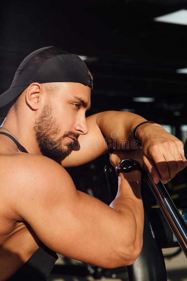 Big strong man fitness model resting in the gym. leaned against the simulator sport equipment. royalty free stock image
