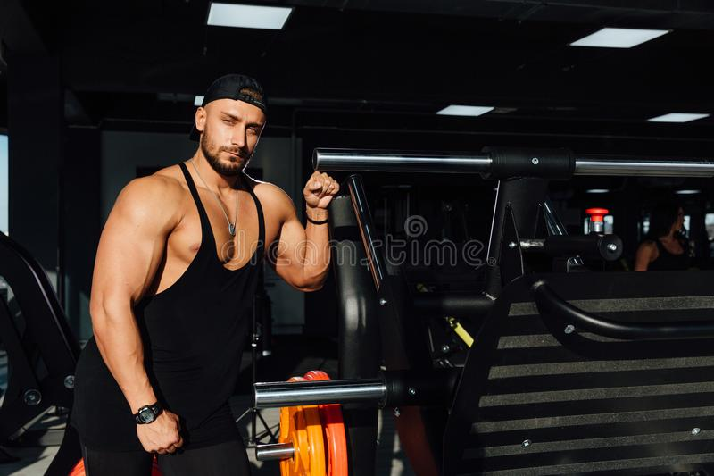 Big strong man fitness model resting in the gym. leaned against the simulator sport equipment. royalty free stock photo