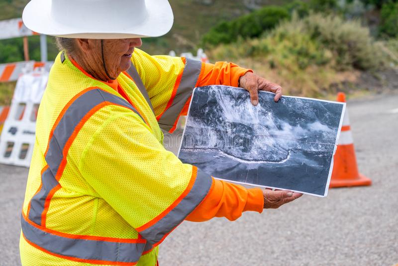 BIG SUR, CA - AUGUST 3, 2017: Woman shows winter landslide damage in Cabrillo Highway. The road is still under construction.  stock photo