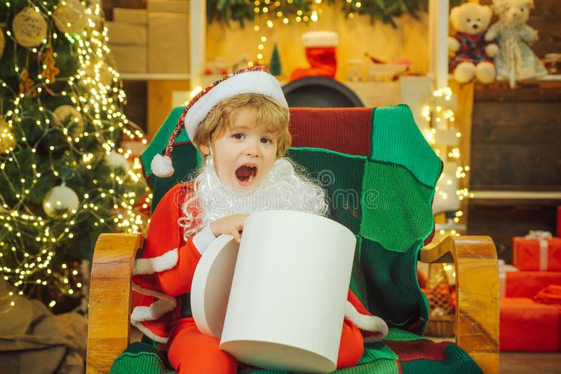 Big surprise for christmas. Boy and a gift in a white box. Child near the Christmas tree. royalty free stock image
