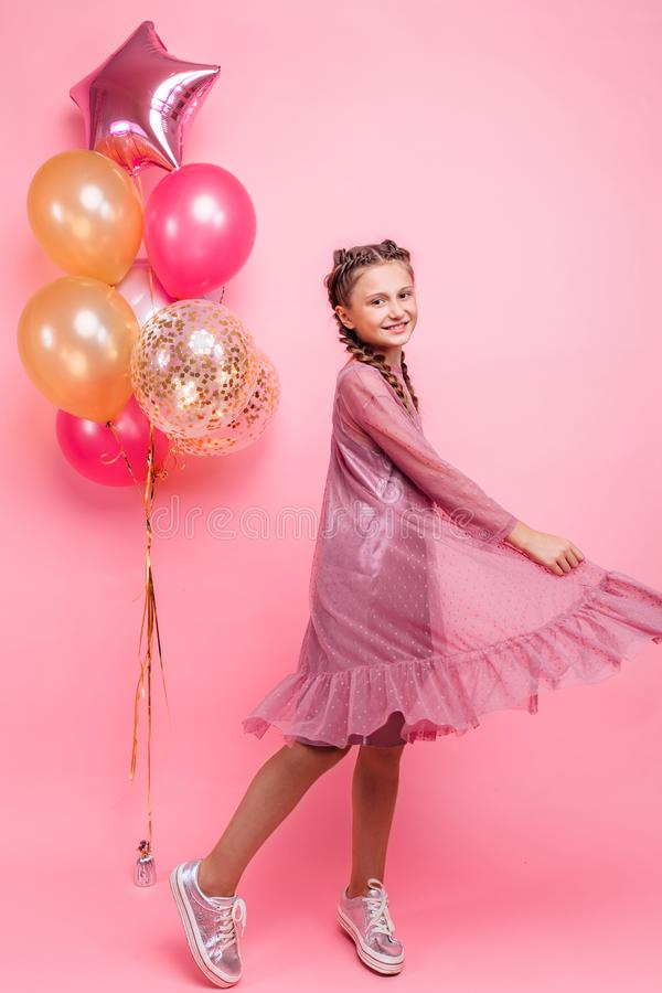 Happy and beautiful teen girl holding a bunch of colorful balloons and looking at camera with smile on pink background royalty free stock photos