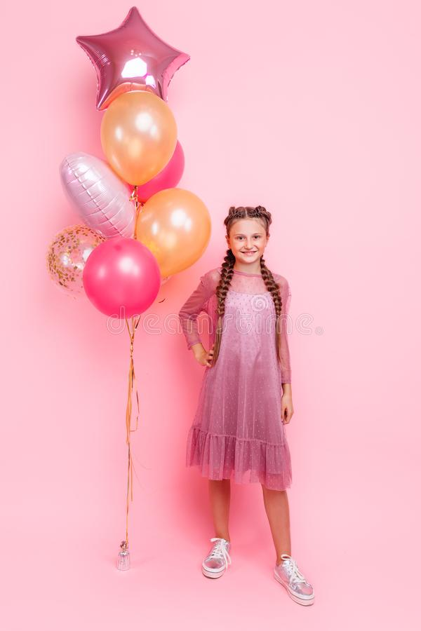 Happy and beautiful teen girl holding a bunch of colorful balloons and looking at camera with smile on pink background stock photo