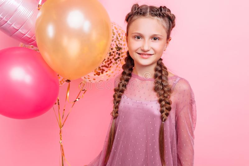 Happy and beautiful teen girl holding a bunch of colorful balloons and looking at camera with smile on pink background stock image