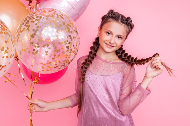 Happy and beautiful teen girl holding a bunch of colorful balloons and looking at camera with smile on pink background stock photography