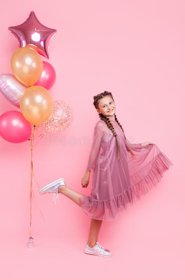 Happy and beautiful teen girl holding a bunch of colorful balloons and looking at camera with smile on pink background stock photos
