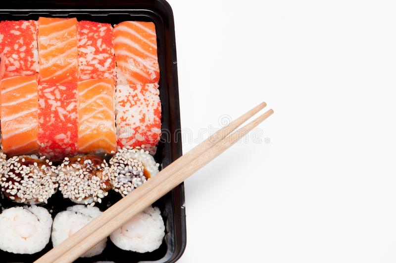 Big sushi set ib black plastic box on white background, top view close up, copy space stock image