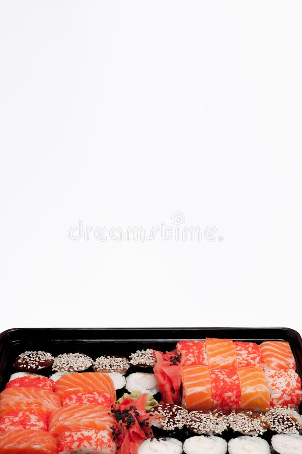 Big sushi set ib black plastic box on white background, top view close up, copy space stock photo